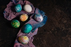 multi-colored Easter eggs of blue tones on a multi-colored cloth background. Easter eggs in low key