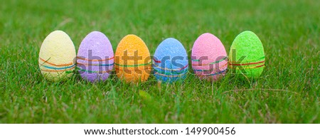 Multi-colored Easter eggs on green grass