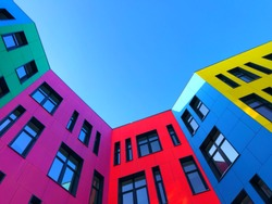 Multi-colored facades of the school with black window frames. Look up from the blue sky