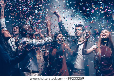 Multi colored fun. Group of beautiful young people throwing colorful confetti while dancing and looking happy