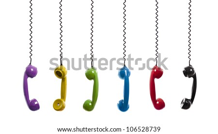 Multi colored handset pieces suspended by the phone cord, isolated on white background
