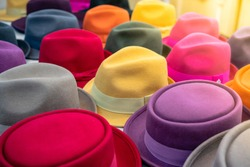 multi-colored hats of different styles on the store counter blurred background