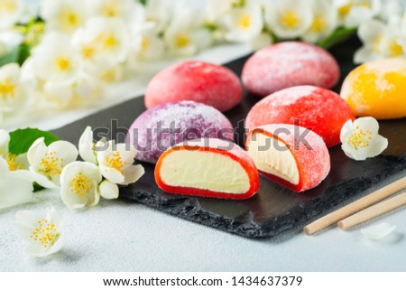 Multi-colored Japanese ice cream Mochi in rice dough and Jasmine flowers on a concrete blue background. Traditional Japanese dessert on a black slate