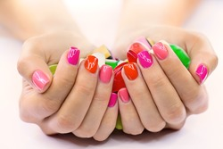 Multi-colored jelly sweets in the hands with a bright nail polish