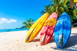 Multi-colored kayaks on a tropical sandy beach. Kayak rental. Tourist entertainment.