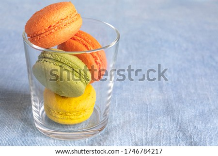 Multi-colored macaroons in a glass cup on a linen napkin. Mcarons or macaroons is French or Italian dessert. Close-up. Copy space