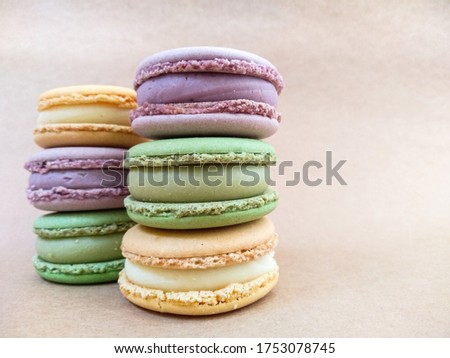 Multi-colored macaroons lie on a beige background. Orange, violet, green macaroon cakes on a light substrate. Background with macaroon. Three macaroons in the foreground and three macaroons blurred.