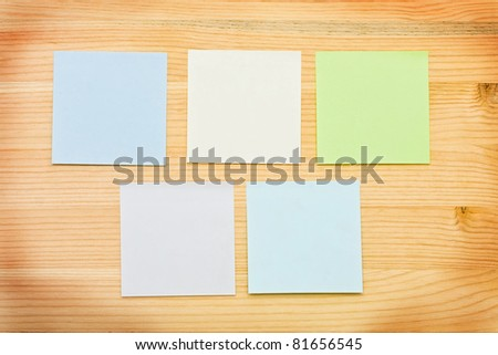 Multi-colored notes on a wooden background