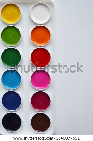 multi-colored paints, multi-colored paper, soft decoration, color stripes on the left side on a white background