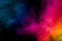 Multi colored particles explosion on black background.Colorful dust splash on dark background.