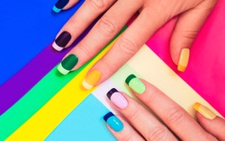 Multi-colored pastel manicure combined tone on tone with a striped background.Nail art.