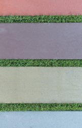 Multi-colored paving slabs. Joints are filled with green grass. Colors - Rosy Brown, Topaz Hue Violet, Tasman Hue Gray, Echo Blue.