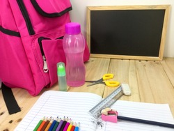 Multi colored pencils, glue, ruler, eraser. pencils, book, bag, scissors and black board on a wooden table background. Education, Examination or Back to School concept.