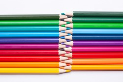 multi-colored rainbow pencils interact with sharp ends isolated on a white background.