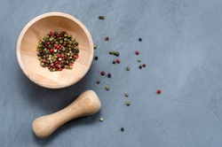 Multi-colored red green black peppercorns in a wooden mortar with a pestle and scattered around on a ultimate gray concrete background close-up with a place for text. seasoning. ingredients.
