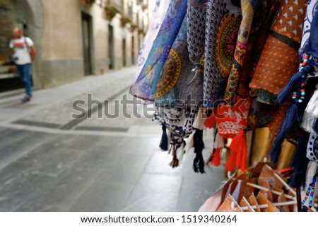 Multi colored scarves hang on the layout of street trading in a tourist place. Travel and consumerism concept