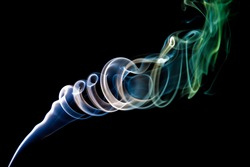 multi-colored smoke in the form of a spiral from aroma sticks on a black background. abstract screensaver. vape smoking. aromatherapy. wallpaper photo