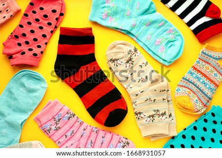 Multi-colored socks on a bright background. Knitted clothes in the form of socks of different sizes on a yellow background. Socks for the cold seasons.