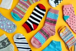 Multi-colored socks on a yellow background. View from above. Many different socks for cold seasons. Socks are scattered on a bright background. Clothes in the form of socks.