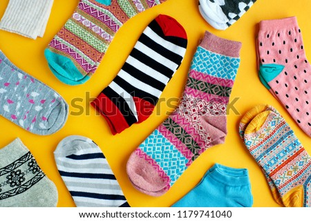 Multi-colored socks on a yellow background. View from above. Many different socks for cold seasons. Socks are scattered on a bright background. Clothes in the form of socks. - Shutterstock ID 1179741040