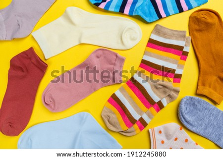 Multi-colored socks on a yellow background. View from above. Many different socks for cold seasons