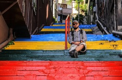 multi-colored steps leading up the stairs, where a man in a beard, shorts, glasses and shirt is sitting. Stairs in the residential area between the houses. the steps are painted in red, green, blue an