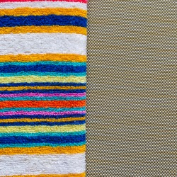 Multi-colored striped beach towel close-up. Colorful rainbow colored towel on a light brown textured background. Positive colors. Abstract background. View from above.