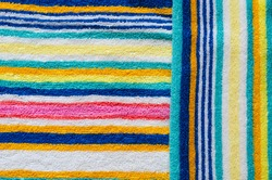 Multi-colored striped beach towel close-up. Colorful towel in rainbow colors. Positive colors. Abstract background. View from above.