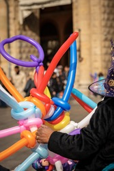 Multi colored sword shaped balloons for sale in Bologna downtown, Italy, during the carnival.