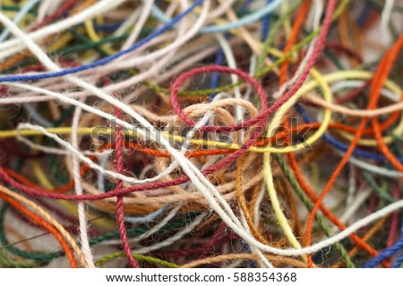 Multi-colored tangled colorful needlecraft silk thread rope. Macro shot. Abstract colors background