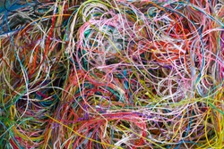 Multi-colored tangled threads abstract texture pattern background. Macro shot of colorful needlecraft silk thread ropes. Colored natural thread pile for sewing clothe scattered randomly like spaghetti