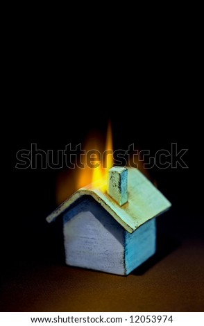 "Multi colored ""toy"" house on fire. Good insurance, banking, real estate, security metaphor"