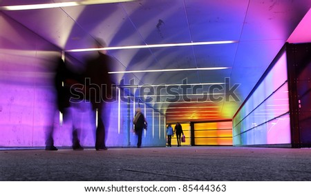 multi colored underground tunnel with people in motion - stock photo