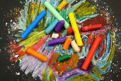 Multi-colored wax crayons lie on a black surface with chaotic crayon drawings on it