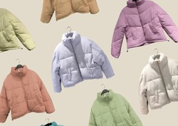 Multi colored women fashion down jacket pattern. A selection of different jackets on hangers isolated on beige background. Winter clothes pattern. Composition of clothes. Flat lay. Padded coat