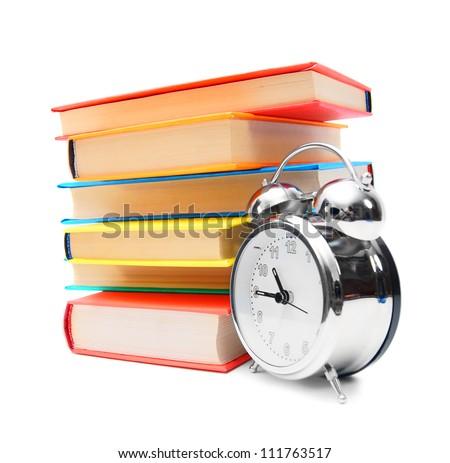 Multi-coloured books and alarm clock.