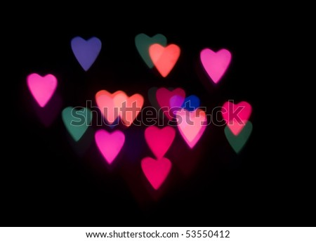 multi coloured heart shaped glowing lights on a black backdrop
