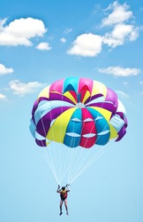 Multi coloured parachute over the blue sky