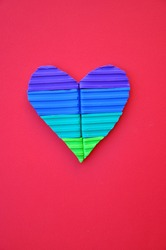 Multi coloured valentines heart made from pieces of plasticine modelling clay against a background of coloured paper. Symbol of romantic love in bright candy colours. Pop art style image