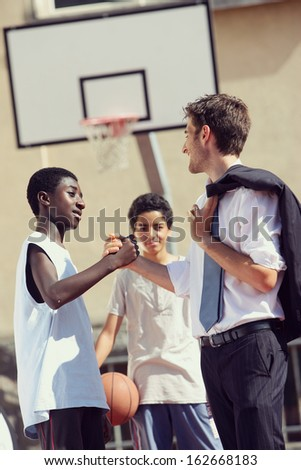 Multi-Ethnic Basketball players shaking hands after match