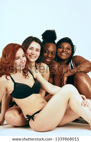 Multi-ethnic beauty. Different ethnicity women - Caucasian, African, Latin, Hispanic beautiful adult smiling girlfriends posing in underwear isolated over white studio background.