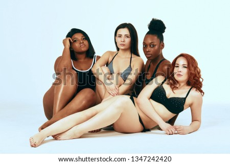 Multi-ethnic beauty. Different ethnicity women - Caucasian, African, Latin, Hispanic beautiful adult girlfriends posing in underwear isolated over white studio background.