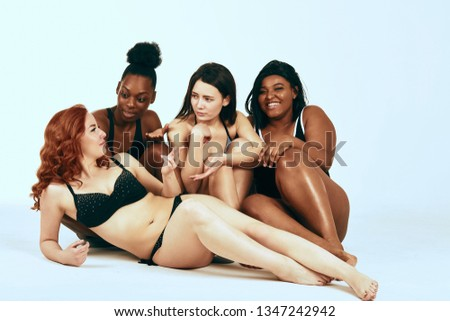 Multi-ethnic beauty. Different ethnicity women - Caucasian, African, Latin, Hispanic beautiful adult girlfriends posing in underwear isolated, chatting together, over white studio background.