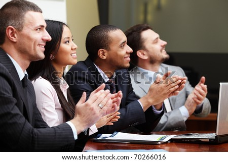 Multi ethnic business group greets somebody with clapping and smiling. Focus on woman - stock photo