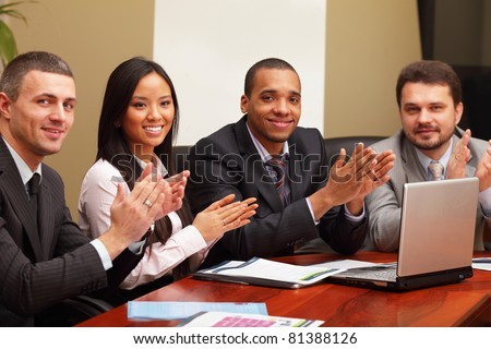 Multi ethnic business group greets you with clapping and smiling. Focus on asian woman