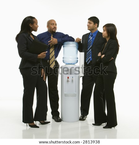 Multi-ethnic business group of men and women standing at water cooler conversing.