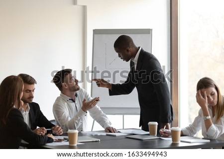 Multi-ethnic business partners having conflict accuse each other at group meeting in boardroom unpleasant situation caused by personal dislike, racial discrimination, struggle for leadership concept Photo stock ©