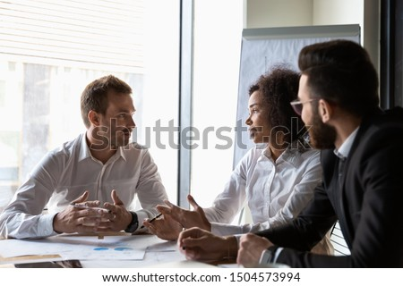Multi-ethnic business partners lead by african chief executive officer analyzing financial situation of company in modern boardroom, corporate financiers reviewing stats and charts at group meeting