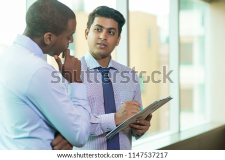 Multi-ethnic business partners working with papers. Handsome young Indian businessman discussing project document with colleague. Daily meeting concept #1147537217