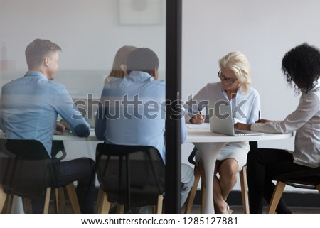 Multi-ethnic business people accomplish important negotiations with contract signing, company representatives and client sitting behind closed doors at modern boardroom, view through the glass wall